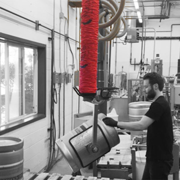 Man lifting a drum / barrel with vacuum lifting equipment in a brewery.