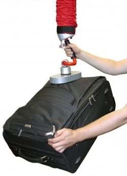 Hands holding a vacuum lifting handle which is lifting baggage.